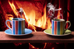 Cups of hot drink in front of warm fireplace. Holiday Christmas concept. Stock Photo