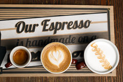 The cups of latte art. On a wooden table Stock Photos