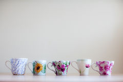 Cups lined up. Cups in a row on a wooden table royalty free stock photos