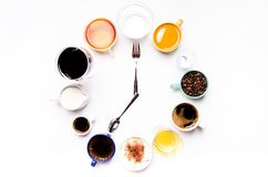 Cups with liquids like a coffee, milk, wine, alcohol, juice stacked in a circle. Clock consist of twelve cups. Time. Alarm clock. Stock Photo