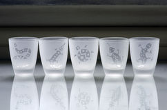 Cups of liquor. Delicate cups of liquor sandblasted with drawings of animals Royalty Free Stock Photos