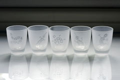Cups of liquor. Delicate cups of liquor sandblasted with drawings of animals Royalty Free Stock Image