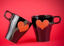 Cups of milk with decorative heart on red background, concept of valentine day Stock Photo