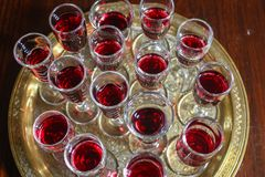 Red wine glasses on a gold tray stock image