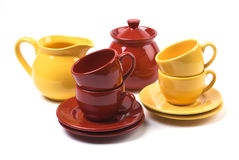 Cups and Saucers. Red and yellow cups, saucers, creamer, and sugar bowl on white background Royalty Free Stock Image