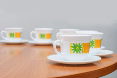 Cups and saucers. On the edge of a round table Royalty Free Stock Photography