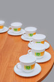 Cups and saucers. On the edge of a round table Stock Photos