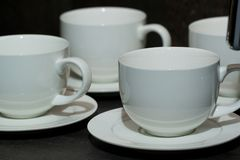 Cups and saucers. Few white cups and saucers for tea or coffee Stock Image