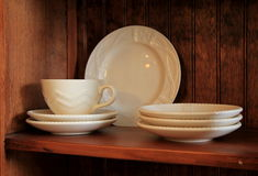 Cups and saucers on wood shelves. White cups and saucers on wood shelves of sideboard in home Stock Photo