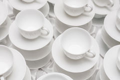 Cups set on saucers in stacks. Stock Image