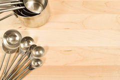 Cups and spoons. Measuring cups and spoons on a wooden background Royalty Free Stock Photography