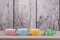 Cups on table over wooden background Royalty Free Stock Image