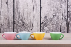 Cups on table over wooden background. Colored cups on table over wooden background royalty free stock photography