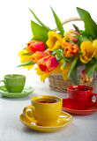 Cups with tea. Colorful cups with tea and tulips in a basket Stock Images