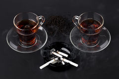 Cups of tea and black ashtray with cigarettes Royalty Free Stock Photos