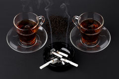 Cups of tea and black ashtray with cigarettes Stock Photo