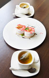 Cups of tea and cakes on a large plate Stock Photo