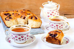 Cups of tea and cherry swirl buns Stock Photography