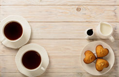 Cups with tea and cupcakes in the shape of a heart on a light wo Royalty Free Stock Photography