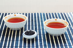 Cups of tea and jar of tea leaves on bamboo table Stock Photography
