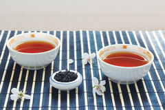 Cups of tea, jar of tea leaves and cherry blossoms Stock Image