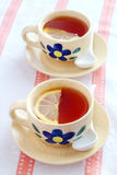 Cups of tea with lemon. Two yellow cups of tea with lemon Stock Photography