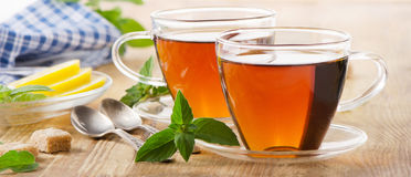 Cups of tea with mint leaves and lemon. Stock Photos