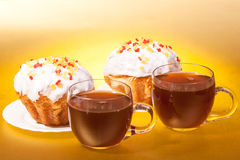 Cups of tea and muffins. On gold background Royalty Free Stock Photos