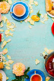 Cups of tea, pot , cakes and flowers petals on light blue background Stock Image