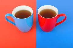 Cups with tea on a red and blue background. Red and blue cups with tea on a red and blue background. Flat lay,top view. Free space for text Stock Photo