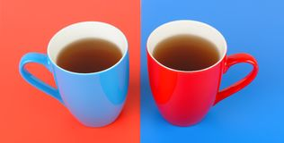 Cups with tea on a red and blue background. Wide photo. Red and blue cups with tea on a red and blue background. Flat lay,top view. Wide photo Stock Photography