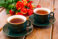 Cups of tea and roses bouquet Royalty Free Stock Photos