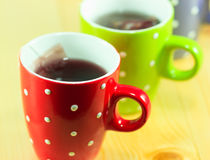 Cups of tea with tea bags Stock Images