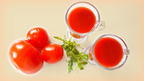 2 cups of tomato juice, arugula herb and some tomatoes on the table. Still life on a white table with tomatoes, arugula herb  and tomato juice in  two glasses Royalty Free Stock Photo