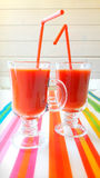 2 cups of tomato juices on the table. Two glasses of tomato juice with straw on bright striped napkin on a background of white wood Stock Image