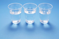 Cups of Water. On Blue Background Royalty Free Stock Images