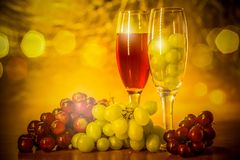 Cups of wine with grapes on a table. Two glasses of wine and grapes on a table use as a background Stock Photography