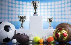 Sport podium, Cups of winners award. Cups of winners award, Sport equipment and balls royalty free stock image