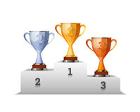 Cups of winners award on white podium Royalty Free Stock Photos