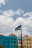 Curaçao señala por medio de una bandera por los edificios coloridos Fotos de archivo libres de regalías