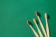 Cura circa ecologia Spazzolini da denti di legno ecologici su un fondo verde Wast zero immagini stock