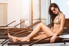 Cura del corpo Donna con l'ente perfetto in bikini che si trova sulla sedia a sdraio dalla piscina Immagine Stock