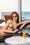 Cura del corpo Donna con l'ente perfetto in bikini che si trova sulla sedia a sdraio dalla piscina Immagini Stock