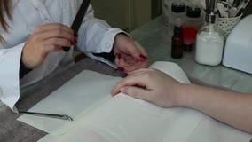 Cura dell'unghia del dito dal manicure ad un cliente della ragazza al salone di bellezza stock footage