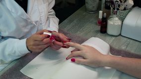 Cura dell'unghia del dito dal manicure ad un cliente della ragazza al salone di bellezza video d archivio