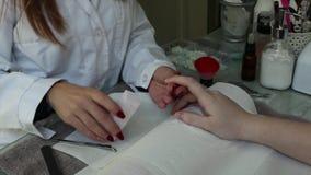 Cura dell'unghia del dito dal manicure ad un cliente della ragazza al salone di bellezza archivi video