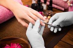 Cura dell'unghia del dito del primo piano dallo specialista del manicure nel salone di bellezza immagini stock libere da diritti