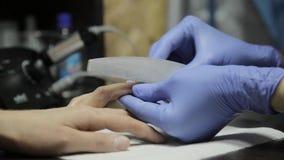 Cura della limatura e della mano dell'unghia La donna passa la ricezione del manicure nel salone di bellezza video d archivio