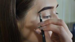 Cura delle sopracciglia Primo piano di bello occhio azzurro della donna, fronte a forma di perfetta, cigli lunghi con trucco prof stock footage