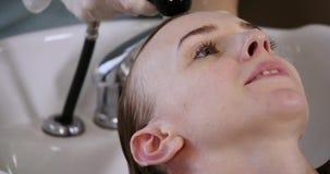 Cura di capelli nella stazione termale moderna donna che fa lavare capelli dal parrucchiere nel salone di capelli Capelli di lava archivi video